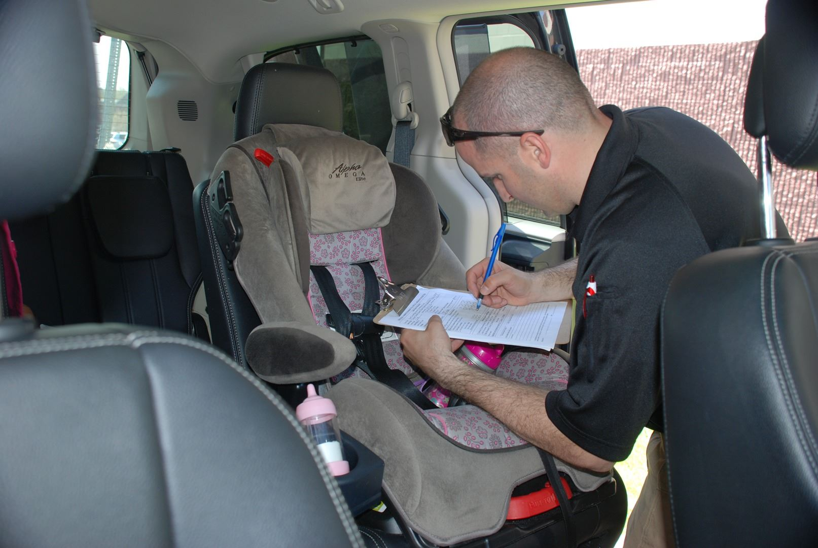 A car seat technician inspects a child safety seat