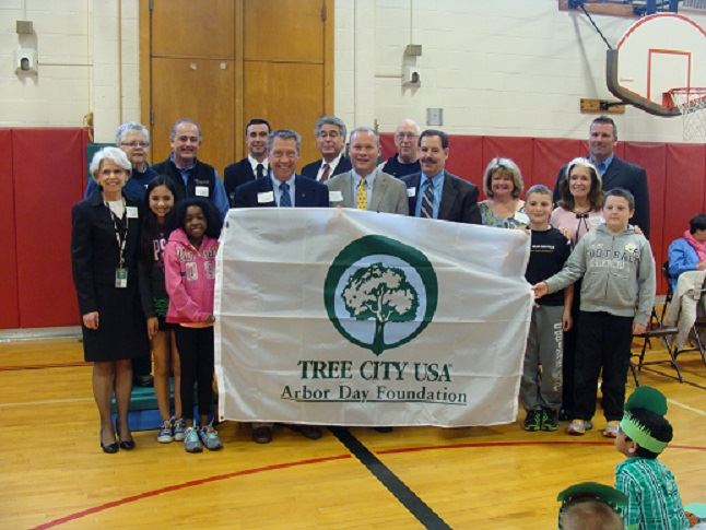 A group of people hold a Tree City USA banner