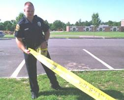 Police Officer putting up yellow police tape